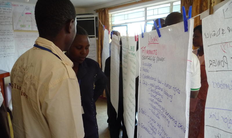 Participants at a Turning the Tide workshop share examples of campaigning success on large pieces of paper.