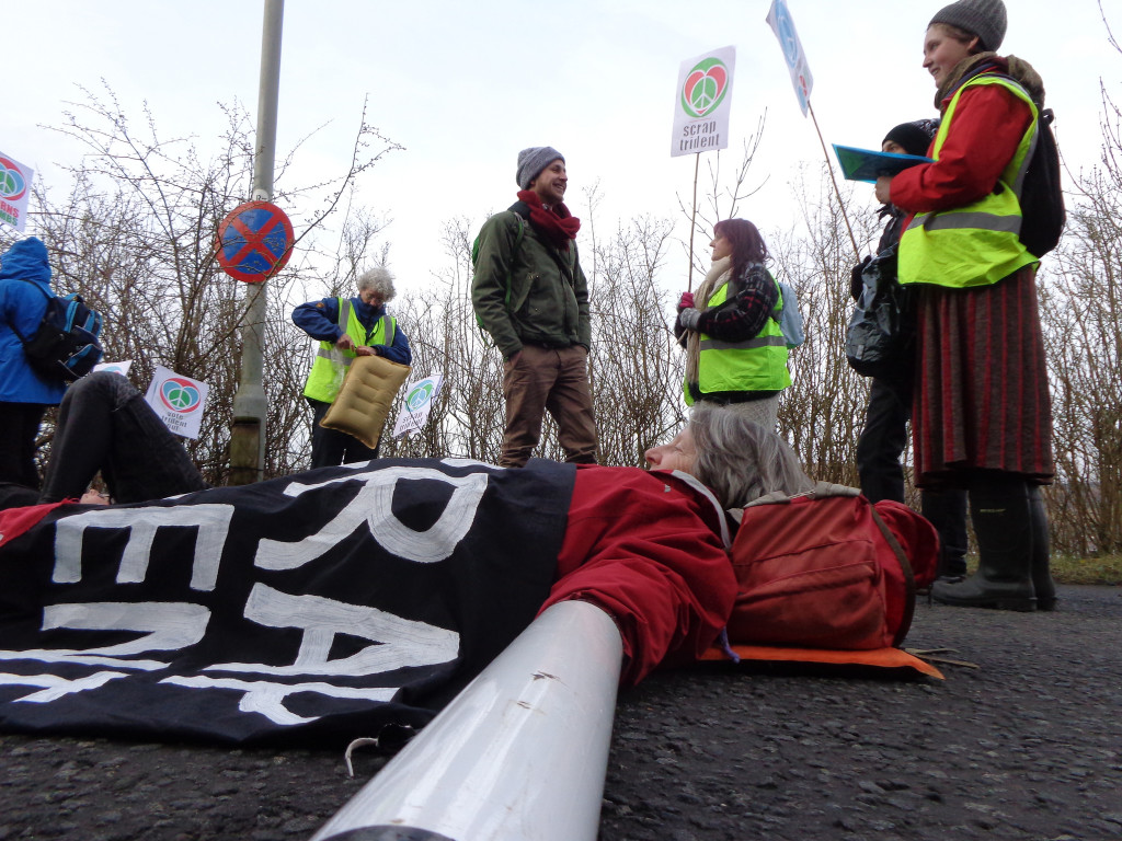 A protestor lies in the road during a blockade of Faslane naval base in 2015