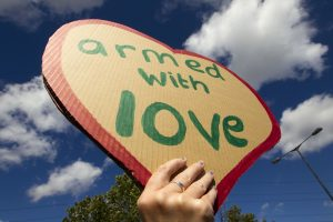 Handmade sign in shape of heart, writing says 'armed with love'.