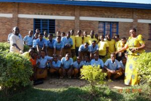 Group photo of around 30 teenagers and school students outside a school in Rwanda.