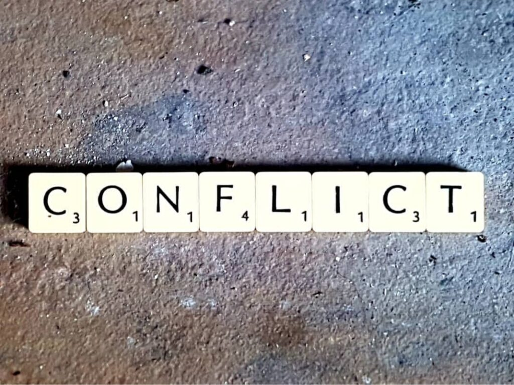 "Scrabble tiles spelling the word ""conflict"" on stone."