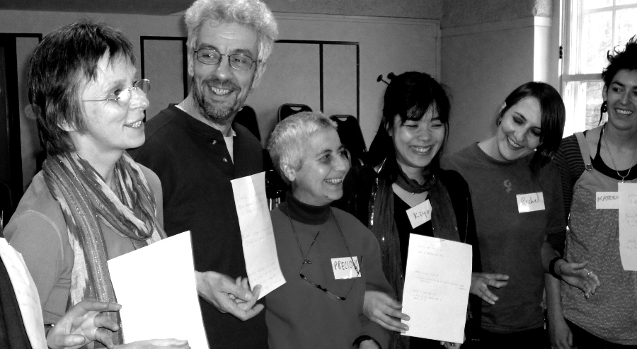 A Turning the Tide trainers' gathering - a row of six people of varying ages smiling and holding up paper